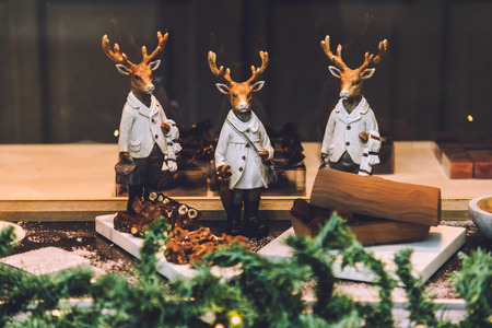animal figurines: Ghent, Belgium - January 1th, 2017. Gent city christmas decorations during winter festival in Flanders. Souvenir shop showcase with stylized deers figurines and pine tree.