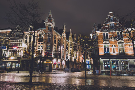 Ghent, Belgium - January 3th, 2017. Medieval flemish city Gent night street of cobblestone with merchant houses, showcases, Christmas illumination, garlands and decorations by Winter festival.