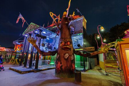 Paris, France - August, 8th, 2017. Psychos attraction of horror in Paris amusement park, located on place de la concorde. Evil ghost house and gigantic haunted tree in french theme park.