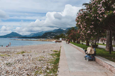 New Bar town, Montenegro - June 5th, 2016. Adriatic sea coast and tourist promenade by cloudy day. Blooming palm alley, mountains and cloudy sky over pedestrian walkway in Bar city.