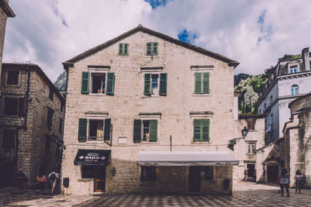 June 2th, 2016 - Kotor, Montenegro. Ancient stone house with green shuttered windows and restaurant on street of Kotor Old Town. 新聞圖片
