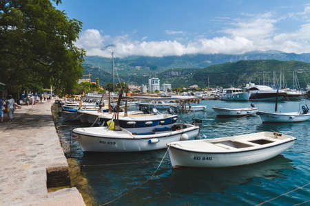 May 30th, 2016 - Budva, Montenegro. Fishing boats on water of Budva port in Montenegro. Private yachts, promenade and marina on mountain background by sunny day in tourist montenegrin capital Budva.