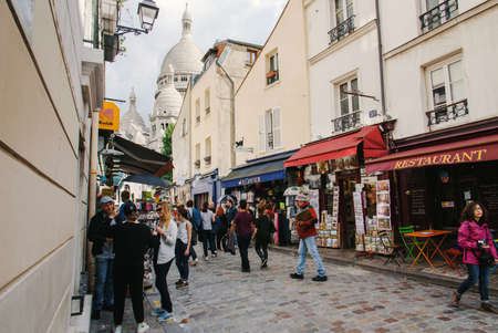 Paris, France - August 10, 2017. Montmartre street leading to Basilica of the Sacred Heart of Paris with people, souvenir shops, restaurant with summer terrace and old classical parisian buildings. 新聞圖片