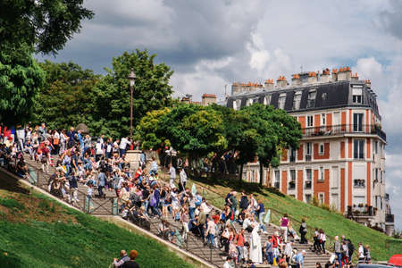 Paris, France - August 10, 2017. Lot of people on steps of Sacre Coeur, Montmartre stairway crowded of people. Crowd of tourist on steps to Basilica of the Sacred Heart of Paris by cloudy day. 新聞圖片