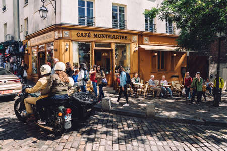 Paris, France - August 10, 2017. Montmartre old Paris street of cobblestone and cafe Montmartre with relaxing people on summer terrace and moving bike in front. Popular french traditional cafe.