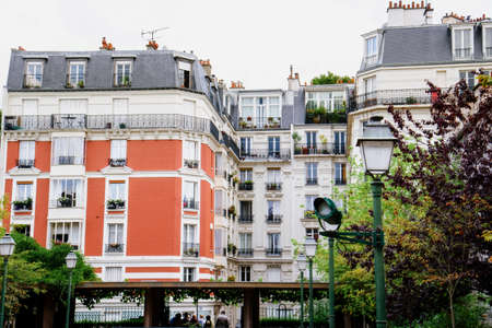 Paris, France - August 10, 2017.Classic Paris houses with french architecture in residential district on Montmartre. White apartment buildings with attic, mansards, greenery and french balconies.