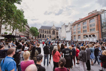 Paris, France - August 11, 2017. People watch street performance in front of whimsical public Stravinsky fountain near centre Georges Pompidou. Urban creativity scene from contemporary parisian life.