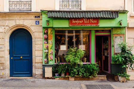 Paris, France - August 13, 2017. Parisian rue Thouin street in the 5th arrondissement and vietnamese restaurant Bonjour Vietnam showcase with greenery.