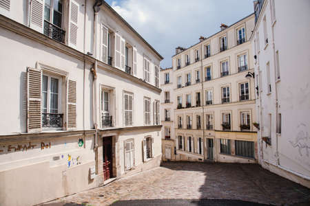Paris, France - August 10, 2017. Cobbled street in Montmartre with old houses of traditional architecture and authentic parisian architectural complex. Narrow french cobblestone street with no people.