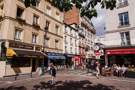 Paris, France - August 13, 2017. Montmartre hill traditional french street scene with relaxing people, outdoor cafes, restaurants with summer terraces and old classical parisian buildings by summer.