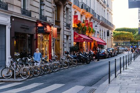Paris, France - August 9, 2017. Narrow french street in Paris with restaurant, boutique, parked scooters and bicycles at dusk. Rue Cambon, classic historic lane with vintage exterior and illumination. 新聞圖片
