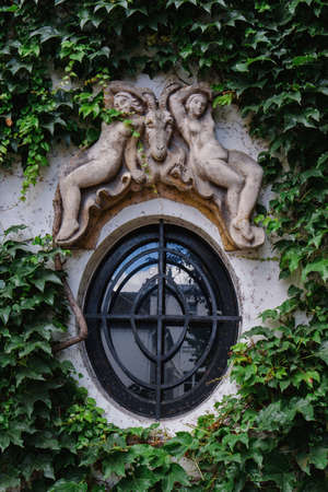 Paris, France - August 10, 2017. Oval window decorated with sculptures and molding with creeping ivy. Ivy window frame on old parisian building on Montmartre hill.