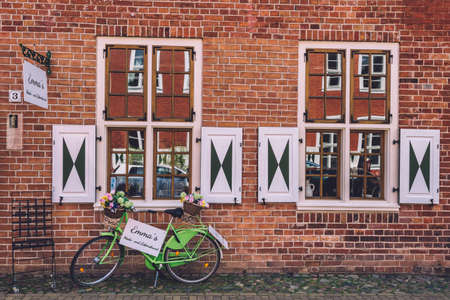 April, 18th, 2017 - Potsdam, Brandenburg, Germany. Old brick house wall, green parked bicycle with flowers and shuttered windows on dutch quarter on Potsdam historic street.