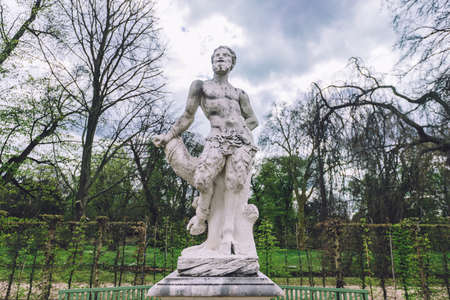 April, 14th, 2017 - Potsdam, Brandenburg, Germany. Antique greek sculpture of satyr in Sanssouci park in Potsdam.