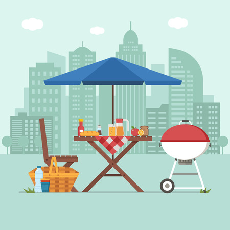 Summer picnic table on city background. Family barbecue concept with picnic party stuff. Bbq grill, straw basket and food for outing on public park.