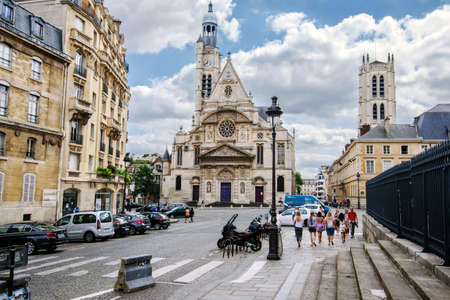 Paris, France - August 13, 2017. Saint Etienne du Mont Church view from Pantheon stair. Place Saint Genevieve in Latin Quarter with french gothic church and walking people by summer.