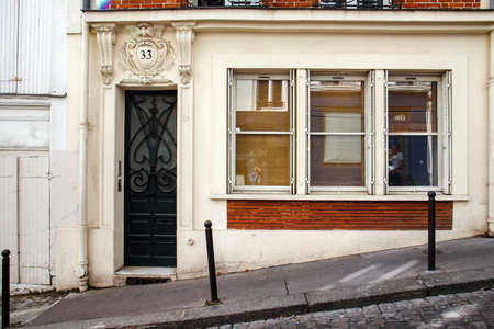 Paris, France - August 10, 2017. Old french house facade with molding and vintage doors on Montmartre hill with no people. Paris picturesque antique front entry door.