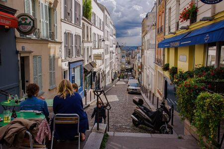 Paris, France - August 10, 2017. Old narrow street of cobblestone, relaxing women on cafe outdoor table, shutter windows and flower pots on the Montmartre historic district by sunny day. Archivio Fotografico - 127947951