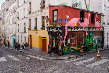 Paris, France - August 10, 2017. Typical cobbled Montmartre street with Le Petit Moulin french traditional cafe facade decorated with flamingo graffiti.
