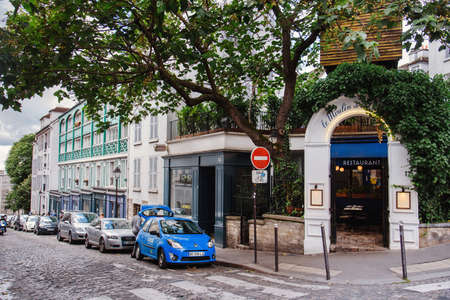 Paris, France - August 10, 2017. Montmartre street and Le Moulin de la Galette restaurant in historical parisian building with greenery, trees and view on Rue Lepic. 新聞圖片