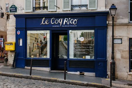 Paris, France - August 10, 2017. Montmartre street and Le Coq Rico restaurant entrance on old classical parisian building facade on Rue Lepic. Montmartre hill french bistro outside view. Archivio Fotografico - 127947953