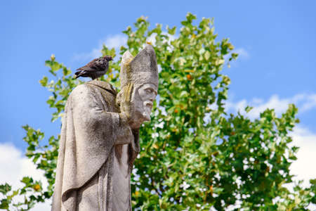 Paris, France - August 10, 2017. Statue of Saint Denis, the first bishop of Paris, martyr holding his head in hands by summer day on Montmartre hill park. Pigeon sitting on beheaded bishops statue.