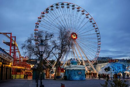 Vienna, Austria - December 29, 2017. Giant Ferris Wheel and winter attractions in viennese amusement park in Christmas Evening. Famous viennese Riesenrad carousel illuminated at dusk.