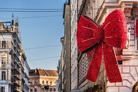 Vienna, Austria - December 29, 2017. Huge Christmas Red bow on Popp and Kretschmer departmental store in Vienna. Giant red ribbon Xmas garland decoration tied building facade.
