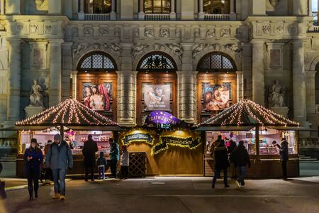 Vienna, Austria - December 25, 2017. People walking at traditional Viennese Christmas market with stall booth at Maria-Theresien-Platz. Kiosks and stands in front of museum of arts in Wien by night.