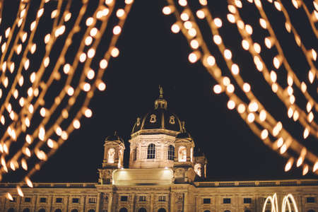 Vienna, Austria - December 25, 2017. Natural History Museum, or Kunsthistorisches framed with illuminated garlands in Christmas. Vienna winter festive fair lights at Maria Theresien Platz by night. 新聞圖片