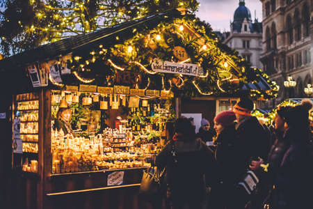 Vienna, Austria - December 24, 2017. People buying souvenirs and gifts at traditional winter Christmas market. Illuminated Xmas fair kiosk with candles near viennese rathaus at dusk. 新聞圖片