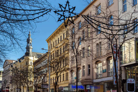 Vienna, Austria - December 29, 2017. Central viennese street with building facades, shops, restaurants, hanging light garlands and seasonal Christmas decoration at sunny day.