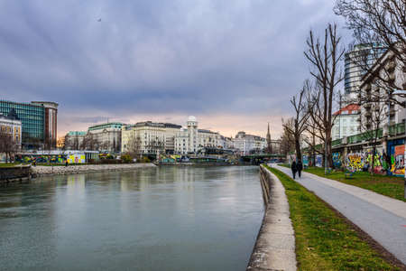 Vienna, Austria - December 29, 2017. Day view of Danube canal flows through Vienna city with Urania Observatory and building facades. Wien river embankment with graffiti and walking people by evening.