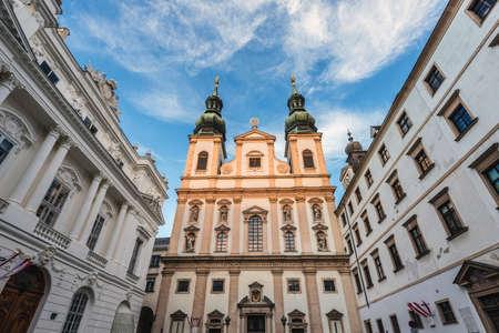 Vienna, Austria - December 31, 2017. View of Jesuit Church double tower. Viennese University church facade in golden evening light.