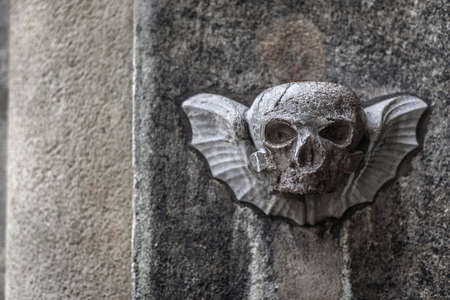 Vienna, Austria - December 30, 2017. Carved stone scull with wings on old church facade wall. Decorative bas-relief sculpture depicts winged mortality sign, life and death old religious symbol.