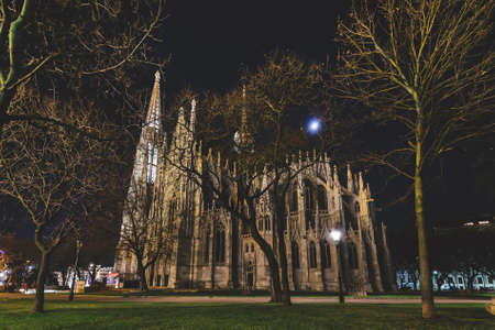 Vienna, Austria - December 25, 2017. Neo - gothic twin tower Votivkirche Illuminated at Night with no people. Facade of gothic Votive church, Sigmund Freud Park park with trees and lampposts at night.