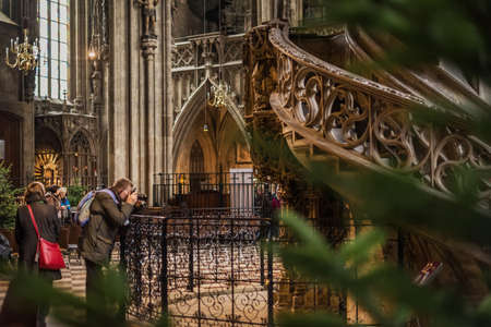 Vienna, Austria - December 30, 2017. Man taking picture with his camera inside Saint Stephens Cathedral with christmas decoration. Church interior with visitors by winter holidays.