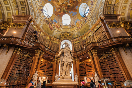 Vienna, Austria - December 24, 2017. Interior of Austrian National Library with emperor Karl VI statue. Hapsburg empires old baroque library Grand Hall with lot of books and walking tourists.