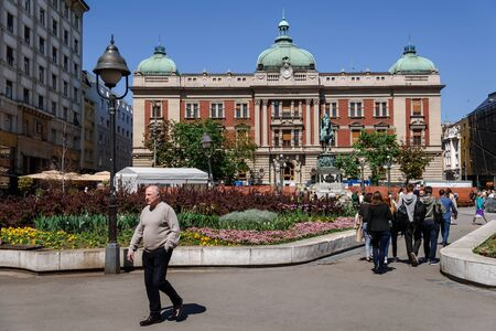 Belgrade, Serbia. April 19, 2018. People walking on central Republic square with National Museum. City scene with Belgrade popular landmark and spring blooming flowers in flowerbeds. 에디토리얼