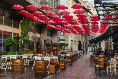 Belgrade, Serbia - June 14, 2018. Outdoor restaurant decoration with hanging red umbrellas in Belgrade center. Popular touristic street cafe with summer terrace and parasols. 에디토리얼