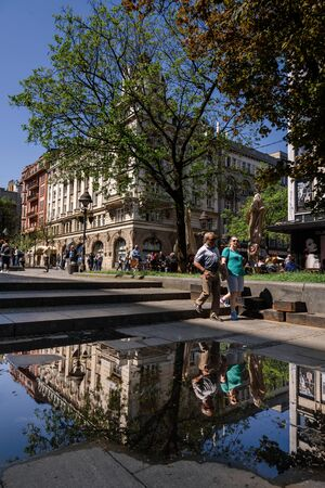 Belgrade, Serbia. April 19, 2018. People walking in central street and reflections in water. City scene with Belgrade architecture, green trees and puddle after spring rain.