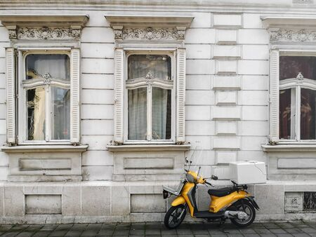 Yellow Scooter Parked near White Vintage Windows