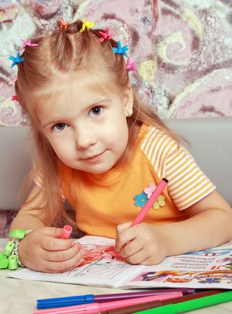 The girl excitedly draws felt-tip pens in the special book