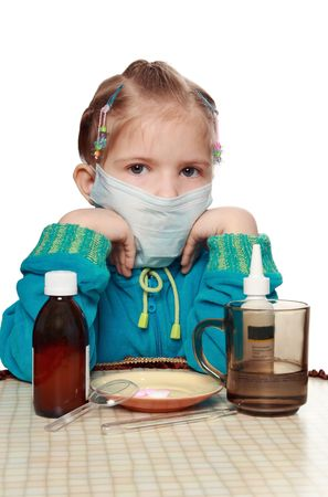 The sad ill girl in a respirator sits at a table with medicines