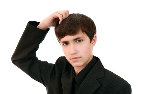 Handsome teenager in a suit thoughtfully combing hair photo
