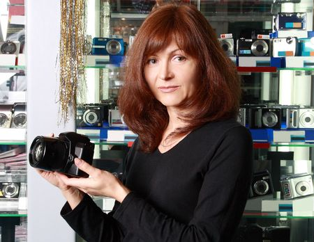 The woman - seller in photographic shop advertises the camera