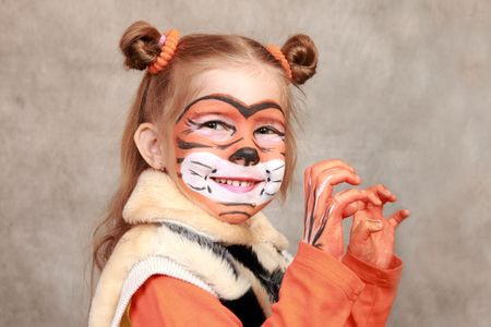 Smiling girl with a painted a tiger face and hands Stock Photo