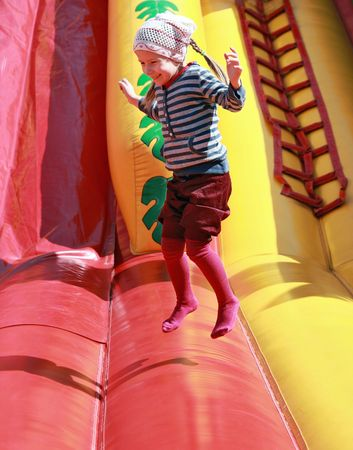Joyful girl jumps on inflatable attractions  photo