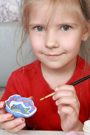 Girl paints a clay crafts