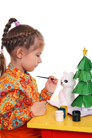 papiermache: A girl paints the figure of a white cat out of papier-mache. Preparing for the New Year
